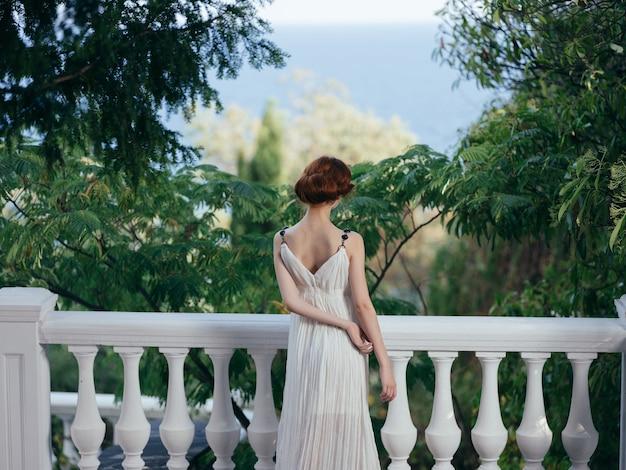 Ładna kobieta w białej sukni i luksusowym wakacyjnym parku w grecji