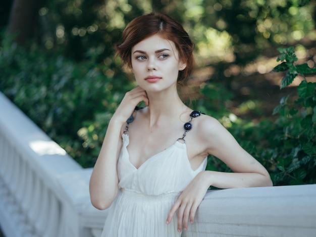 Ładna kobieta w białej sukni księżniczki w letnim parku
