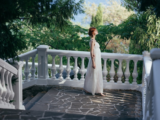 Ładna kobieta w białej sukni pozowanie w greckiej mitologii parku. zdjęcie wysokiej jakości