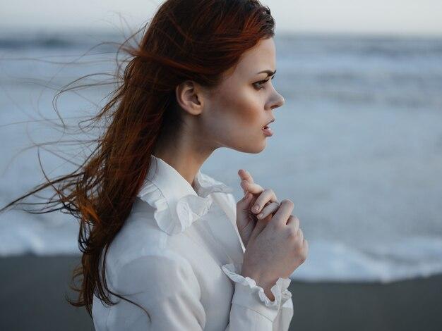 Ładna kobieta w białej sukni pozuje luksusowo spacerując po plaży