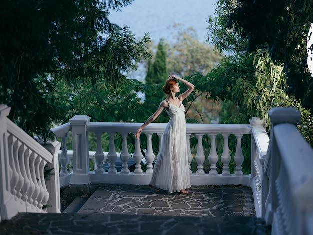 Ładna kobieta w białej sukni pozuje w mitologii parku grecja