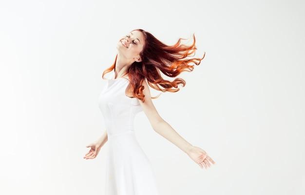 Ładna kobieta w białej sukni rude włosy glamour ruch