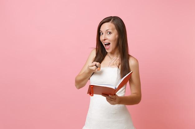 Ładna kobieta w białej sukni trzymająca z przodu pamiętnik, notatnik i wskazujący ołówek