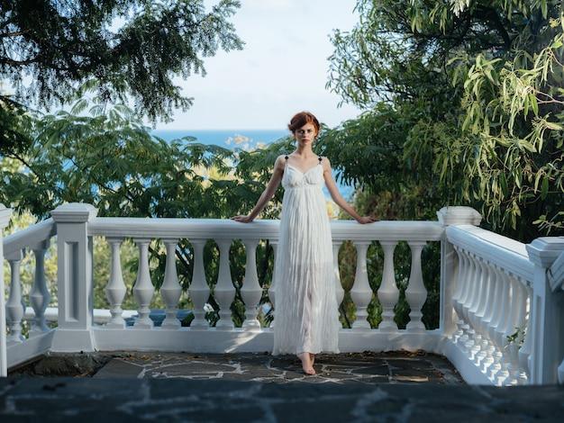 Ładna kobieta w białej sukni w parku grecja dekoracji księżniczka