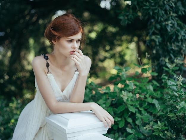 Ładna kobieta w białej sukni z zielonymi liśćmi modelka glamour