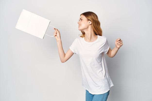 Ładna kobieta w białej t-shirtowej torbie na zakupy w rękach