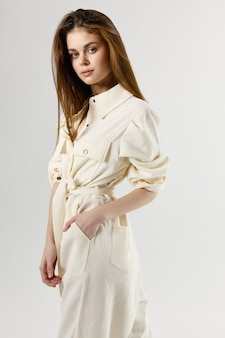 Ładna kobieta w białym kombinezonie trzyma rękę w kieszeni