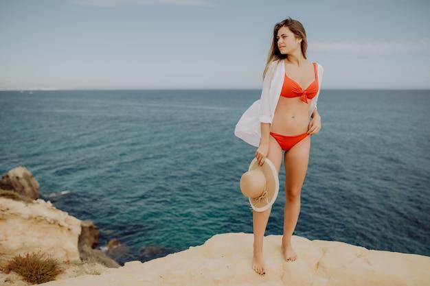 Ładna kobieta w bikini i słomkowym kapeluszu odpoczywa na skraju góry