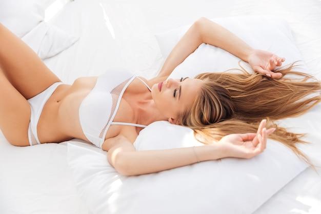Ładna kobieta w bikini leżąca na łóżku z odrobiną prześcieradła