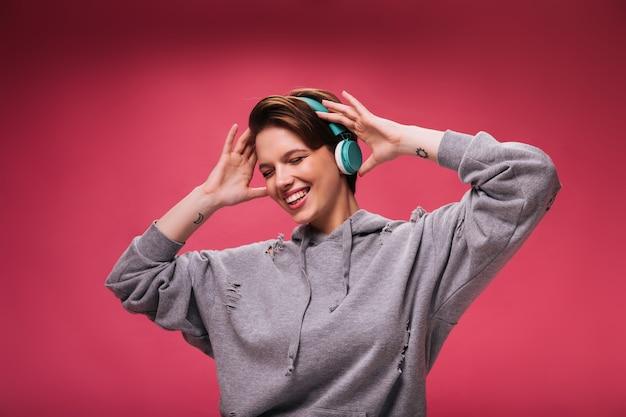 Ładna kobieta w bluza z kapturem, słuchanie muzyki w słuchawkach na różowym tle. teen dziewczyna w szarej bluzie tańczy i uśmiecha się na na białym tle