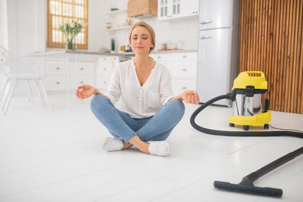 Ładna kobieta w bluzkę i dżinsy w pozycji lotosu na białej podłodze w domu po czyszczeniu