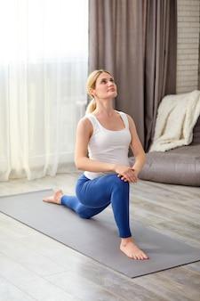 Ładna kobieta w ciąży rozciągająca nogi i całe ciało