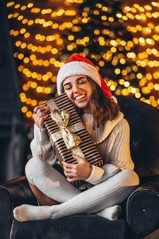 Ładna kobieta w ciepły sweter, skarpetki i świąteczny kapelusz, siedząc na krześle w domu z pudełkiem