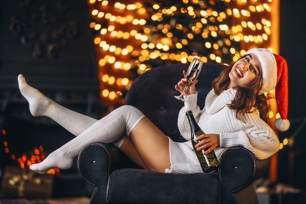 Ładna kobieta w ciepłym swetrze, skarpetkach i świątecznej czapce, siedząca na krześle z szampanem