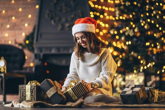 Ładna kobieta w ciepłym swetrze, skarpetkach i świątecznej czapce, siedząca na podłodze