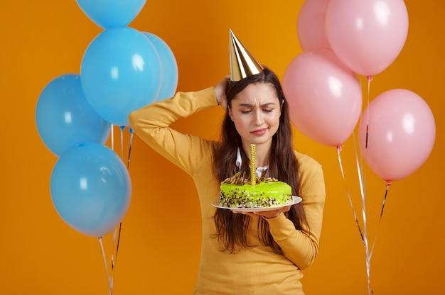 Ładna kobieta w czapce gospodarstwa tort urodzinowy z fajerwerkami, żółte tło. uśmiechnięty mężczyzna dostał niespodziankę, uroczystość, dekorację balonów