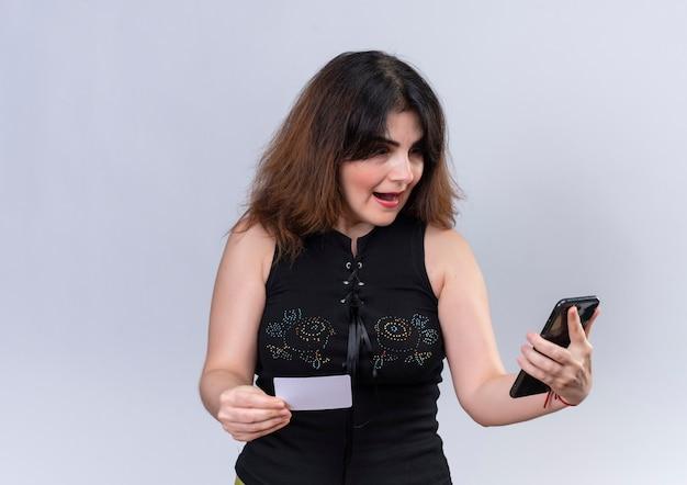 Ładna kobieta w czarnej bluzce patrzy na telefon zaskoczony trzymaniem karty