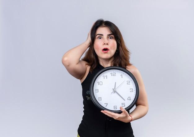 Ładna kobieta w czarnej bluzce trzyma zegar wygląda na zmartwioną spóźnieniem