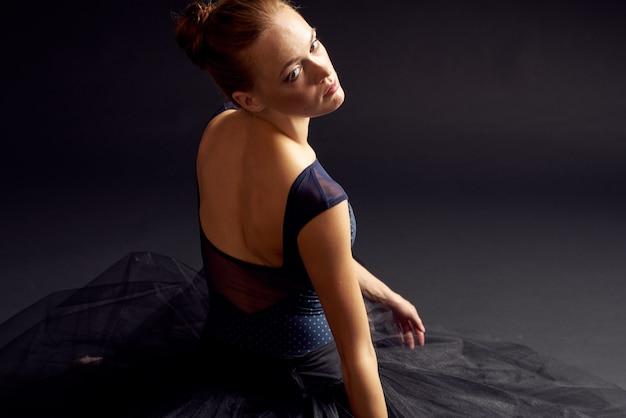 Ładna kobieta w czarnej sukience taniec moda wykonywania ciemnym tle. zdjęcie wysokiej jakości