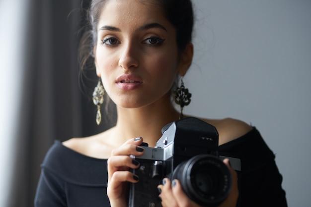 Ładna kobieta w czarnej sukience w pobliżu okna pozowanie modelki