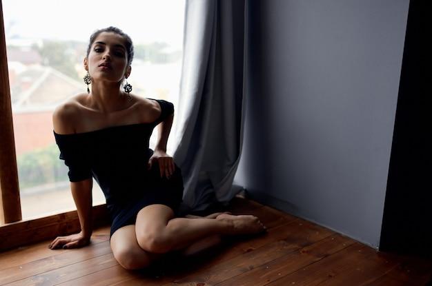 Ładna kobieta w czarnej sukience w pobliżu okna pozowanie studio stylu życia. zdjęcie wysokiej jakości