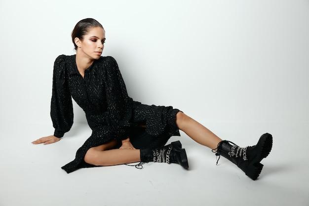 Ładna kobieta w czarnej sukni siedzi na tle glamour moda na białym tle podłogi