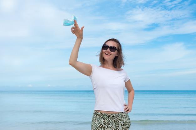 Ładna kobieta w czarnych okularach przeciwsłonecznych, trzymając maskę medyczną