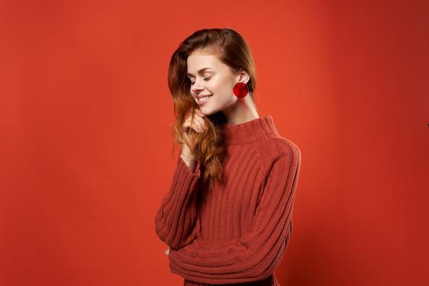 Ładna kobieta w czerwone kolczyki sweter urok biżuteria na białym tle