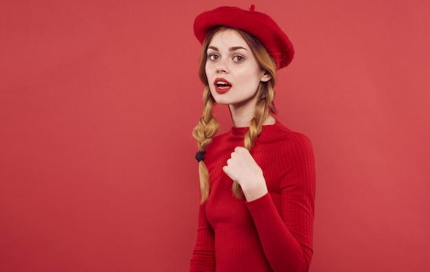 Ładna kobieta w czerwonej sukience czapki warkocze czerwone tło.