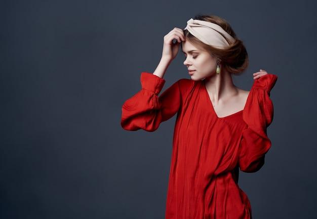 Ładna kobieta w czerwonej sukience i kosmetykach do dekoracji opaski