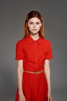 Ładna kobieta w czerwonej sukience moda elegancki styl na białym tle