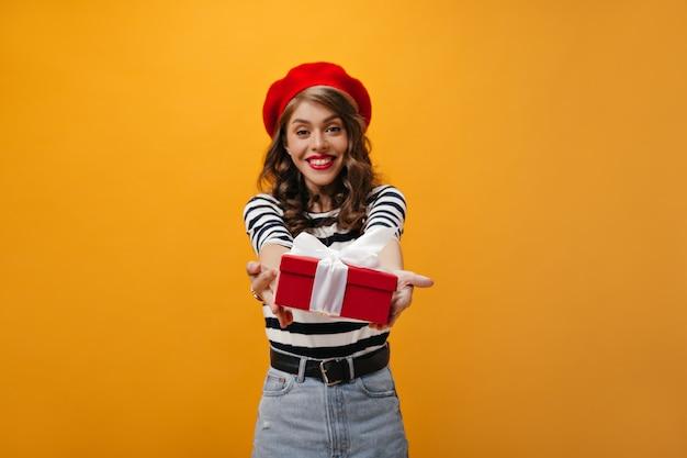 Ładna kobieta w czerwonym berecie demonstruje pudełko dziewczyny. szczęśliwa dziewczyna z falowanymi włosami w nowoczesne ubrania, uśmiechając się na pomarańczowym tle.