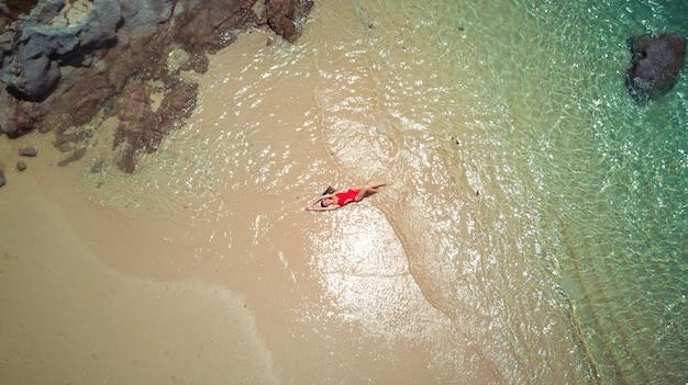 Ładna kobieta w czerwonym bikini kostium kąpielowy lubi wodę morską, brązowy piasek. widok z lotu ptaka wykonany przez drona. zdjęcie z lotu ptaka