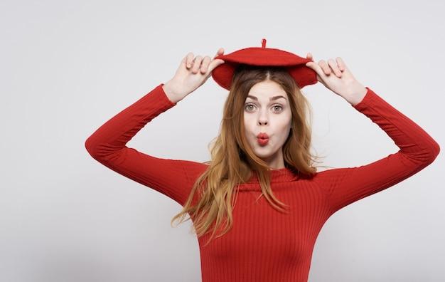 Ładna kobieta w czerwonym kapeluszu trzymająca modę uroku włosów