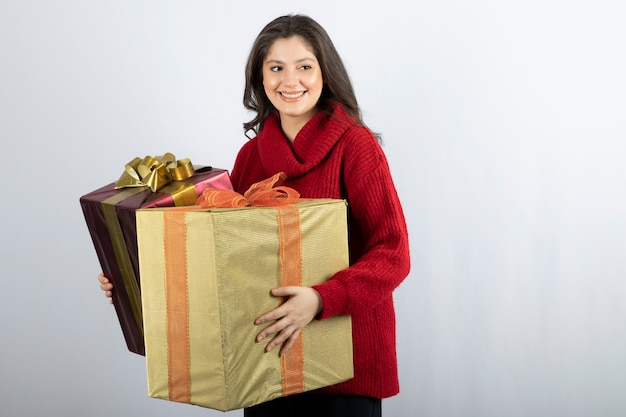 Ładna kobieta w czerwonym swetrze trzyma prezenty świąteczne.