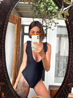Ładna kobieta w domu robi zdjęcie selfie w lustrze na telefonie komórkowym, aby znaleźć historie i posty w mediach społecznościowych, ubrana w czarny letni strój kąpielowy