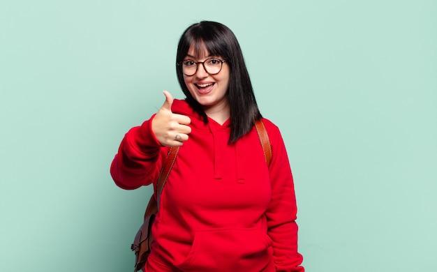 Ładna kobieta w dużych rozmiarach czuje się dumna, beztroska, pewna siebie i szczęśliwa, uśmiechając się pozytywnie z kciukami w górę