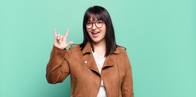 Ładna kobieta w dużych rozmiarach czuje się szczęśliwa, zabawna, pewna siebie, pozytywna i zbuntowana, wykonując ręką rockowy lub heavy metalowy znak