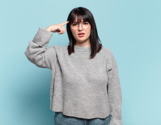 Ładna kobieta w dużych rozmiarach czuje się zdezorientowana i zdezorientowana, pokazując, że jesteś szalony, szalony lub oszalały