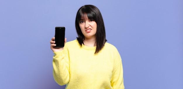 Ładna kobieta w dużych rozmiarach czuje się zdezorientowana i zdezorientowana, z tępym, oszołomionym wyrazem twarzy, patrzącą na coś nieoczekiwanego