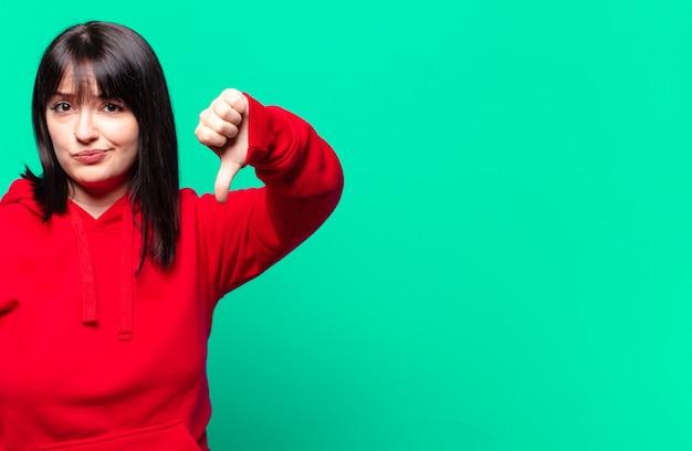 Ładna kobieta w dużych rozmiarach czuje się zła, zła, zirytowana, rozczarowana lub niezadowolona, pokazując kciuk w dół z poważnym spojrzeniem