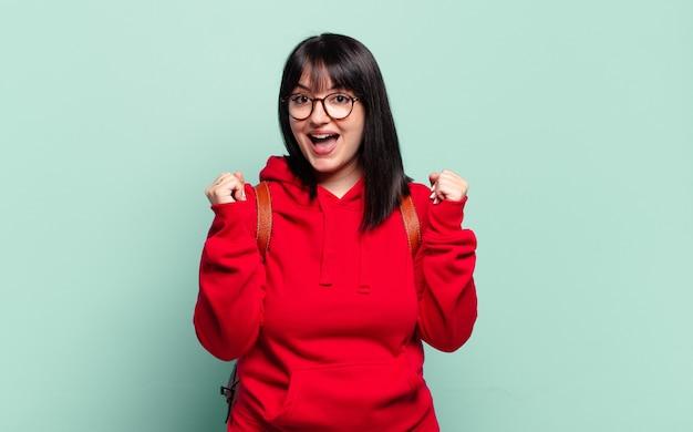 Ładna kobieta w dużych rozmiarach czuje się zszokowana, podekscytowana i szczęśliwa, śmieje się i świętuje sukces, mówiąc wow!