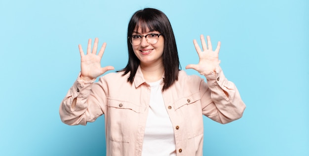Ładna kobieta w dużych rozmiarach, uśmiechnięta i wyglądająca przyjaźnie, pokazująca cyfrę dziesiątą lub dziesiątą z ręką do przodu, odliczającą w dół