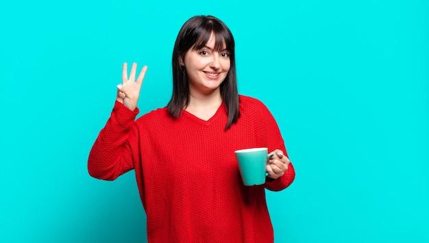 Ładna kobieta w dużych rozmiarach, uśmiechnięta i wyglądająca przyjaźnie, pokazująca numer trzy lub trzeci z ręką do przodu, odliczając w dół
