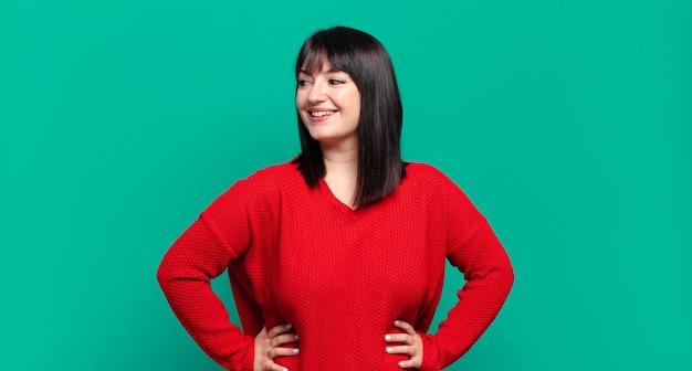 Ładna kobieta w dużych rozmiarach, wyglądająca na szczęśliwą, pogodną i pewną siebie, uśmiechającą się dumnie i patrzącą na bok z obiema rękami na biodrach