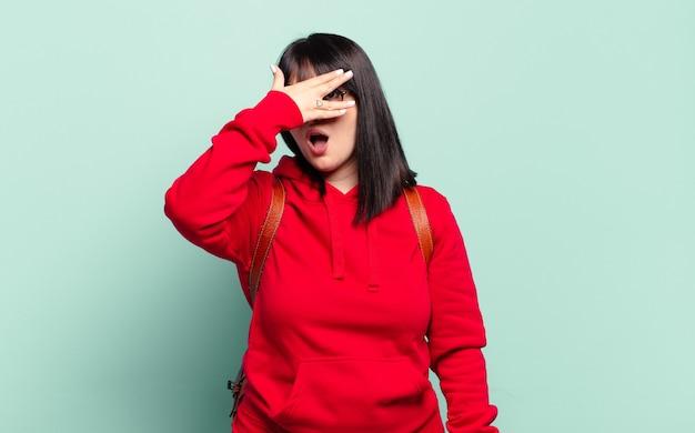 Ładna kobieta w dużych rozmiarach, wyglądająca na zszokowaną, przestraszoną lub przerażoną, zakrywa twarz dłonią i zerka między palcami