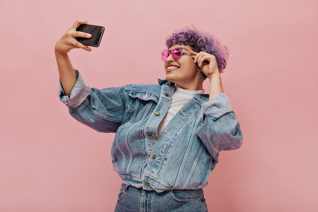 Ładna kobieta w dżinsowym garniturze i uśmiechach w jaskraworóżowych okularach przeciwsłonecznych. kobieta trzyma swój smartfon i bierze selfie.