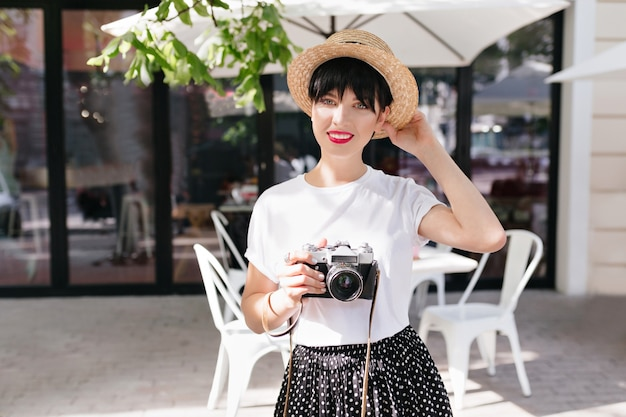 Ładna kobieta w elegancki kapelusz słomkowy z uroczym uśmiechem w ręku pozuje na ulicy