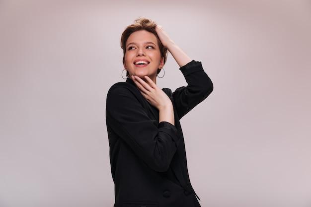 Ładna kobieta w garniturze pozowanie na białym tle. portret atrakcyjna pani w czarnej kurtce, śmiejąc się na na białym tle