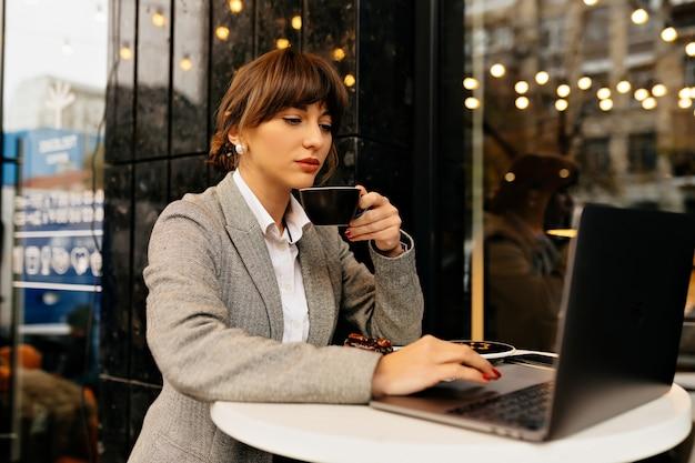 Ładna kobieta w garniturze ze słuchawkami i działaniem laptopa